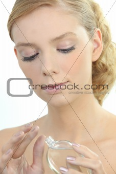 Blonde woman with bottle of perfume