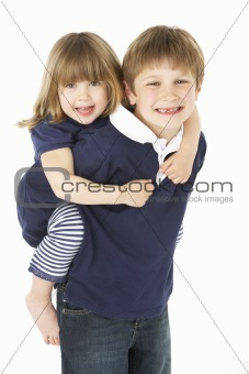 Studio Portrait Of Brother Giving Sister Piggy Back