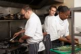 Team Of Chefs Preparing Food In Restaurant Kitchen