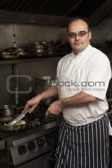 Male Chef Preparing Meal On Cooker In Restaurant Kitchen