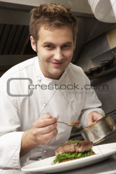 Chef Adding Sauce To Dish In Restaurant Kitchen