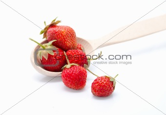 The wooden spoon with the fresh strawberries