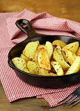 fresh potatoes fried in a pan on a wooden table