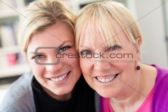 mother and daughter hugging, looking at camera