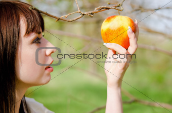 Portrait of beautiful young girl picking the apple