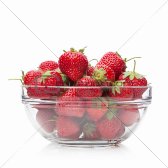 Fresh strawberries in a glass dish on white.