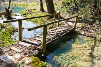 Wooden bridge on the path beside the river.