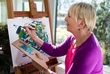 Happy elderly woman painting for fun at home