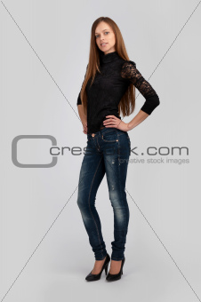 happy young woman standing on gray background