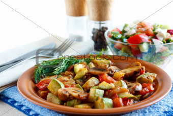 Roasted vegetables on a rustic plate. Salad with fresh vegetables in the background