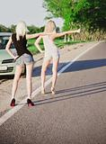 Two sexy blonde girls standing near their broken car and hitchhiking