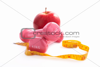 Apple and dumbbells  with a measuring tape.
