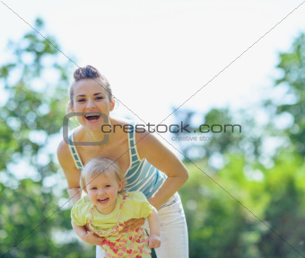 Happy mother and baby playing outside