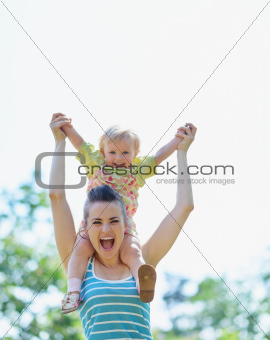 Happy mother with baby sitting on shoulders