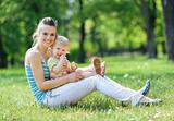 Happy mother and baby sitting on grass in park