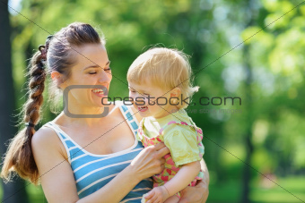 Happy mother tickling baby outside