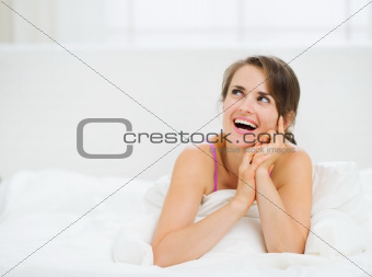 Smiling woman laying in bed and looking on copy space