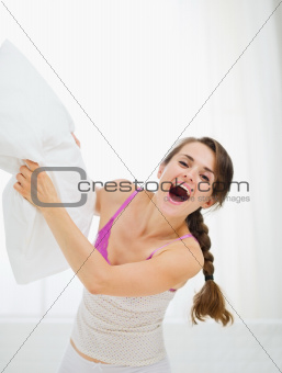 Happy girl pillow fighting