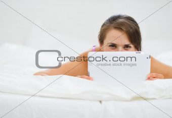 Smiling woman laying in bed and hiding tablet PC