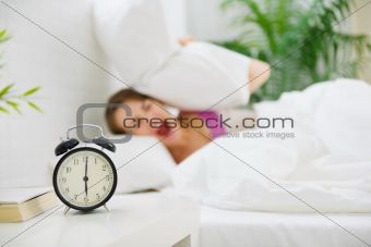 Upset woman closing ears by pillow to avoid hearing alarm clock