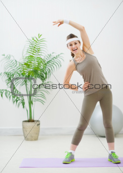 Smiling fitness woman making stretching exercises