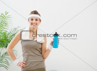 Portrait of smiling healthy woman with bottle of water
