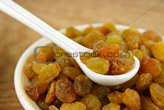 Raisins in the spoon on a plate of raisins