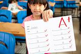 smiling little girl showing exam paper with a plus in the classroom