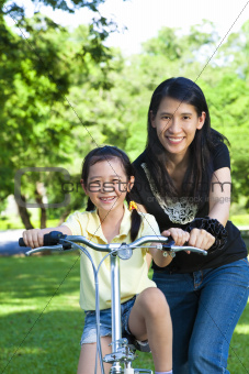 asian mother Teaching daughter To Ride A bicycle