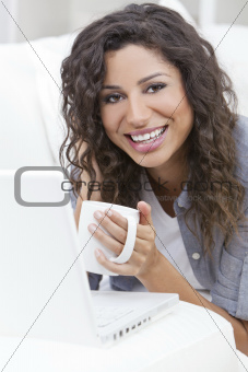 Woman Smiling Drinking Tea or Coffee Using Laptop Computer