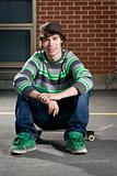 Skateboarder sitting on board