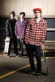 Three skateboarder kids standing in parking lot