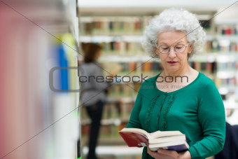 senior woman reading and choosing book in library