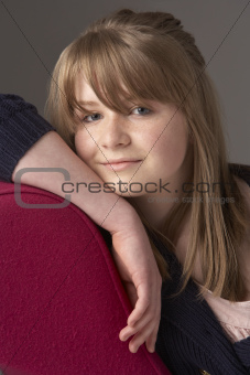 Thoughtful Teenage Girl Relaxing On Chaise Longue