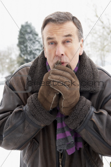 Senior Man Standing Outside In Snowy Landscape Warming Hands