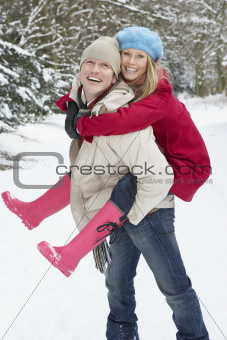 Man Giving Woman Piggyback In Snowy Woodland