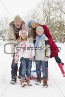 Family Pulling Sledge Through Snowy Landscape