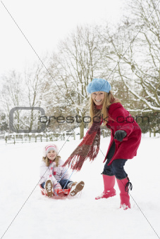 Mother Pulling Daughter On Sledge Through Snowy Landscape