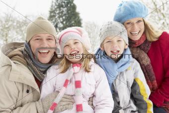 Family Sitting In Snowy Landscape