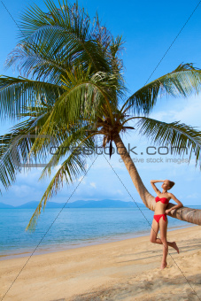 Woman leaning against a palm tree