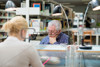 Senior man studying among young people in library
