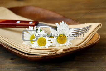 wooden plate and daisy on wooden background