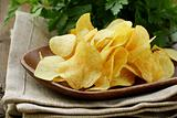 potato chips in wooden plate , on a wooden table