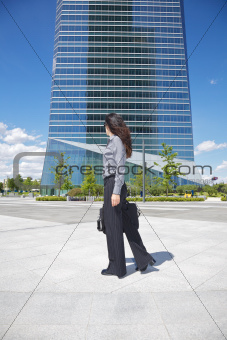 businesswoman walking next to skyscraper