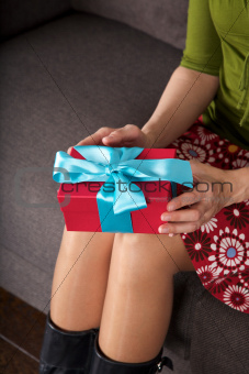 holding present sitting on sofa