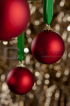 Three red Christmas baubles in front of a gold glitter backgroun