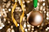 Single golden Christmas bauble in front of a gold glitter backgr