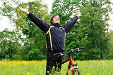 Excited happy man among the green nature with hands outstretched