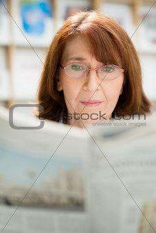 Elderly woman with glasses reading newspaper in library