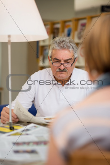 Senior man reading newspaper with wife in library